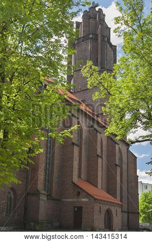Poland Silesia GliwiceAll Saints church seen from north sunlit trees in may