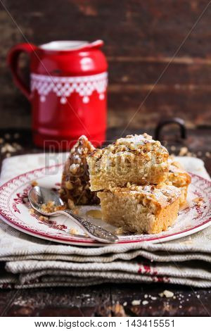 Cake with walnuts and maple syrup on a plate, selective focus