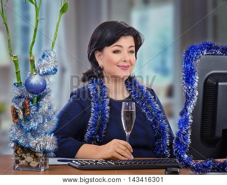Smiling mature woman sits at the desk with glass of white wine in her hand and looks at monitor. Black haired woman wears navy color dress decorated by dark blue silver Christmas tinsel garland. There are keyboard, glass vase with bamboo, mobile phone on
