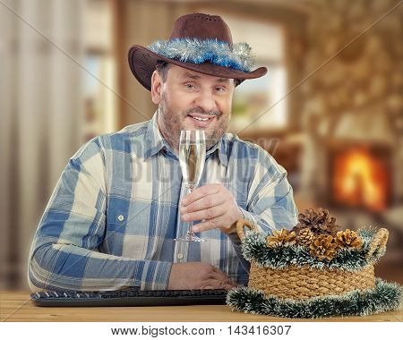 Middle-aged smiling cowboy gives Christmas toast looks at camera. He sits at the desk says a few words with glass of white wine in his hand. The man wears blue plaid shirt and brown hat decorated with tinsel garland. There are keyboard, basket with pine c