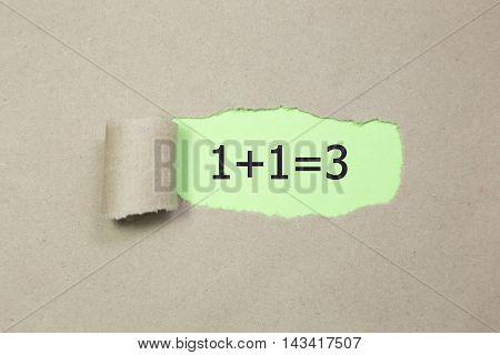 1+1=3 written under torn Brown paper.Business, technology, internet concept