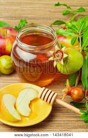Honey jar with wooden stick and apples with pomegranate