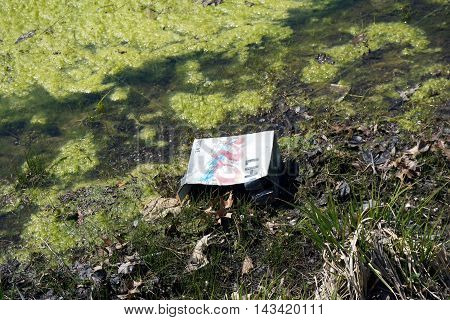 JOLIET, ILLINOIS / UNITED STATES - APRIL 16, 2016: A faded, discarded beer case sits at the edge of a small lake in Joliet's Wesmere Country Club subdivision.