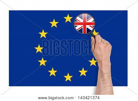 Top view of a man's hand holding a magnifier over EU flag with magnified flag of UK. Brexit. British withdrawal. Significant decision. Substantial choice.