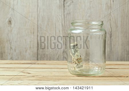 Money in glass jar on wooden table