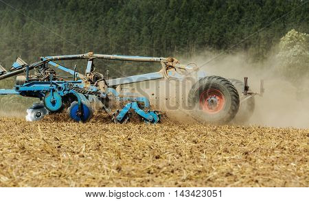 Tractor cultivating field at spring. Tractor with cultivator handles field before planting