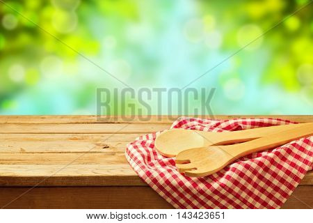 Kitchen utensil and checked cloth over garden bokeh background