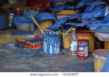 Artist's tools and paints in a studio. Paint droplets and smears on a dark background.