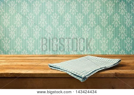 Tablecloth on wooden table over retro wallpaper