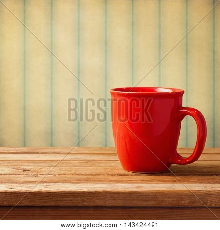 Vintage background with red coffee mug on wooden table