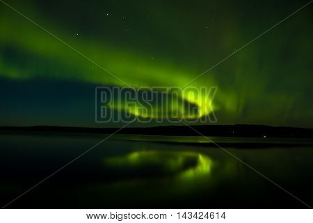 emerald green northern lights refection on lake