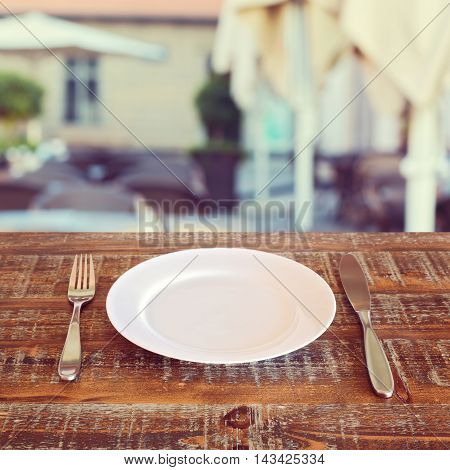 Restaurant background with empty plate and silverware