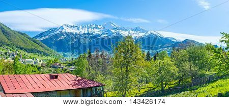 The snowbound peaks of Caucasus mountains from the green valley ocuupied by townlets and villages with the medieval towers of Mestia on the distance Svaneti Georgia.
