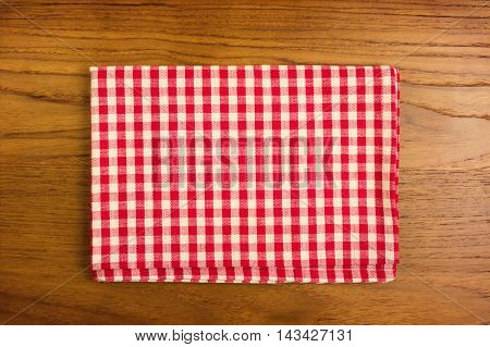 Checked red tablecloth on empty wooden table