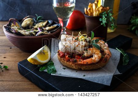 Appetizer with spicy tomato squids and shrimps on toast, close view