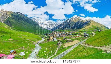 The amazing mountain village of Zhibiani with the narrow and twisted Enguri river and snowy Shkhara Mount on the background Ushguli Upper Svaneti Georgia.