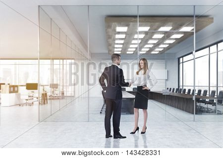 Man and woman shaking hands near conference room in office. Concept of introduction. 3d rendering. Mock up. Toned image