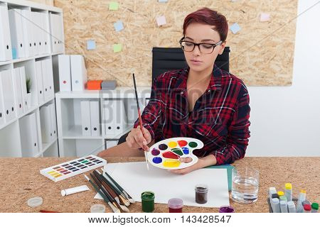 Woman painter getting ready for class in college. She is sitting in her office with cork board and mixing paint. Concept of art education and aesthetics