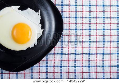 Top View On A Black Plate With A Fried Egg With A Yolk
