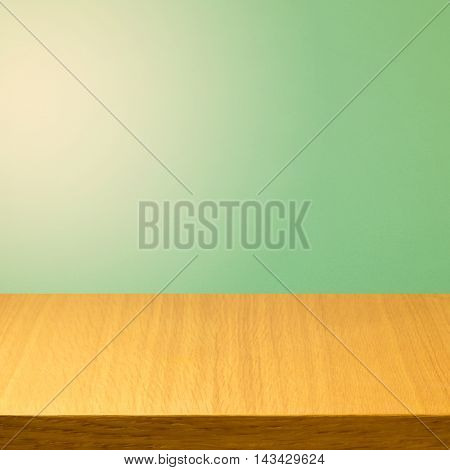 Empty wooden modern table over green solid color background