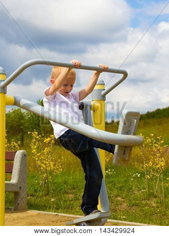 Kid having fun in playground. Boy stretching on air walker. Child playing outdoor. Active childhood.
