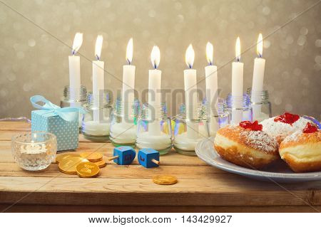 Jewish holiday Hanukkah table setting with donuts and candles