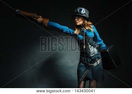 Weapon victorian style vintage concept. Subculture girl in outfit. Steam punk lady with blunderbuss and briefcase aiming for threat.