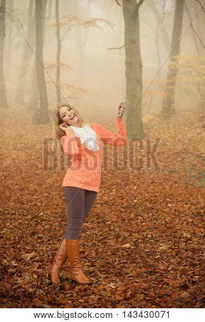 Young woman with earphones and smartphone listening to music. Happy girl relaxing enjoying in foggy fall autumn park. Leisure pleasure and technology concept.