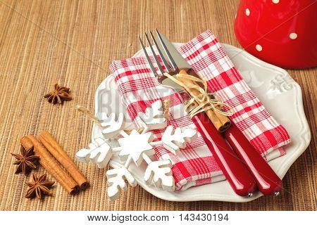 Christmas table setting with decorations, checked red cloth and plate