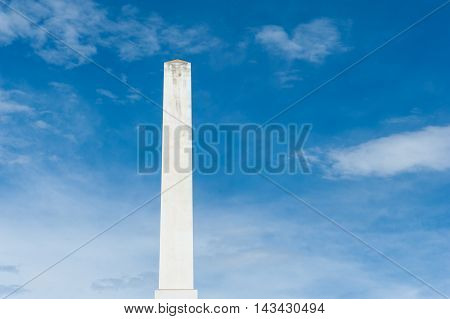 White marble obelisk on blue sky and clouds masculine power and strength concept
