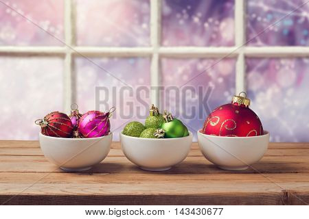 Christmas balls on wooden table over window background