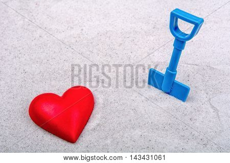 Red heart and blue scoop on a grey sand background