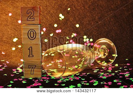 2017 in wooden blocks displayed with pink and green confetti and a champagne glass on a black background