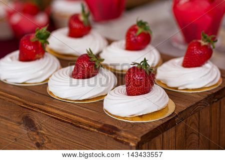Meringue cake with strawberries on the wedding table. Food