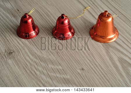 Red bells to decorate a Christmas tree isolated against a wooden background