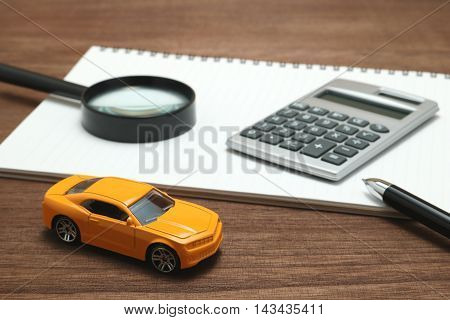 +++NOTE TO INSPECTOR: THE ITEMS USED IN THIS IMAGE ARE GENERIC AND PURCHASED AT A DISCOUNT SHOP+++ Toy car, magnifying glass, calculator, pen and notebook. Rent, buy or insurance car concept.