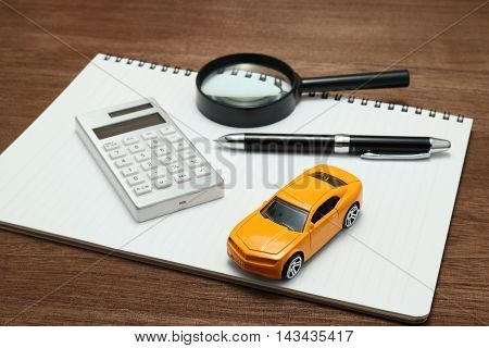 Toy car, magnifying glass, calculator, pen and notebook. Rent, buy or insurance car concept.