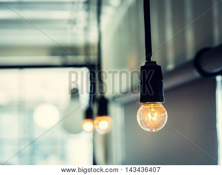 Row of illuminated retro light bulb decoration. Photo with vintage style tone.