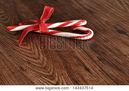 Candy canes with a red bow isolated on a wooden background