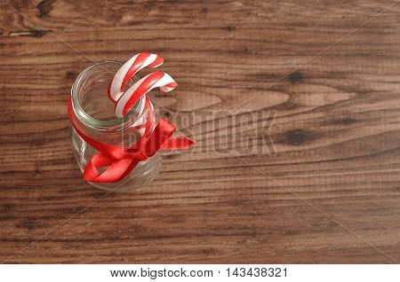 Two Candy canes displayed in a bottle