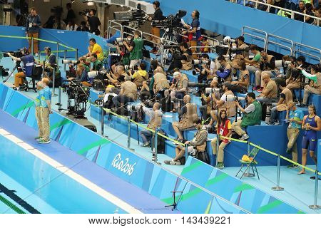 RIO DE JANEIRO, BRAZIL - AUGUST 10, 2016: Professional sport photographers during the Rio 2016 Olympic Games at the Olympic Aquatics Stadium