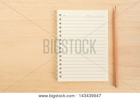 Top view of open spiral line paper notebook and sharp brown pencil on light wooden background