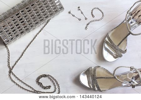 Women's set of fashion accessories in silver color on wooden background: shoes handbag and jewelry