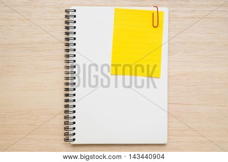 Yellow line memo note clipped on a white open spiral notebook on wooden background