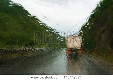 Low visibility driving concept. Wet windscreen with heavy rain and track on slippery road ahead. Raindrops on windshield of moving car on highway. Abstract blurred bad weather vehicle driving