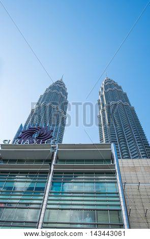 KUALA LUMPUR MALAYSIA - FEBRUARY 29: Bottom view of Petronas twin towers on February 29 2016 in Kuala Lumpur Malaysia. Petronas Twin Towers with Suria KLCC Mall.