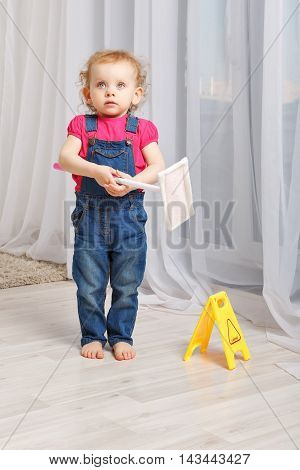 Girl washed mop the floors in the room. Small mother's helper. Household chores. Girl waiting for the approval of mother.