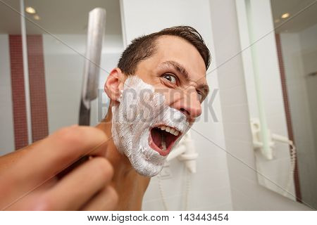Man is holding a straight razor. Mad man. On the face of shaving cream.