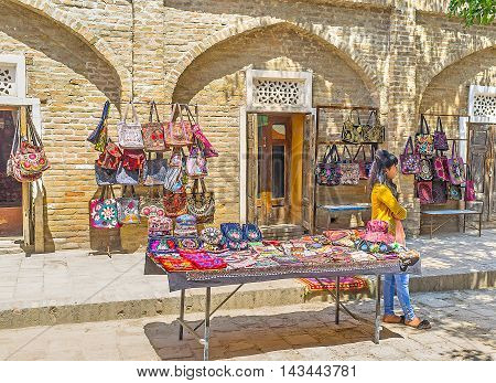SHAKHRISABZ UZBEKISTAN - MAY 2 2015: The stall with the handmade colored bags decorated with the floral embroideries on May 2 in Shakhrisabz.
