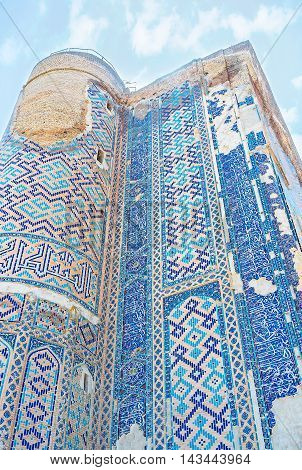 The old walls of Ak-Saray Palace covered with the geometric patterns and islamic inscriptions on blue glazed tile Shakhrisabz Uzbekistan.